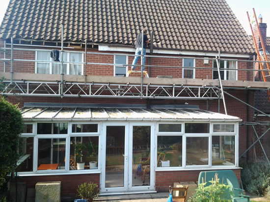 Old wooden fascias and old gutters being removed.